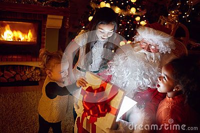 Sanat Claus and three little girls opening a magical Christmas g