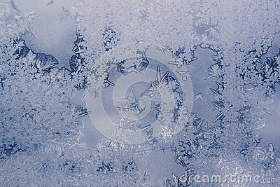 Winter background with icy frost patterns on the window.
