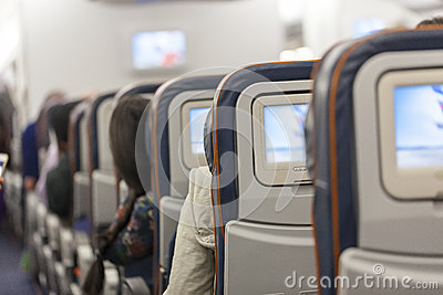 Seating space with multimedia screens economy class airplane cabin