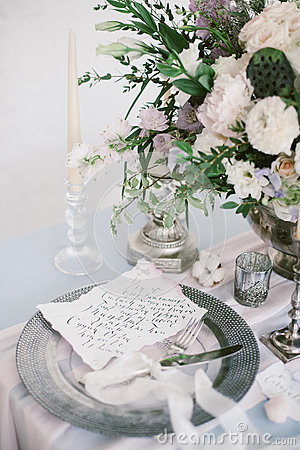 Graphic arts of beautiful wedding calligraphy cards and silver plate with cutlery.