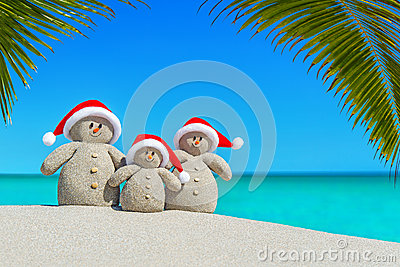 Christmas sandy Snowmen family in Santa hats at palm beach.