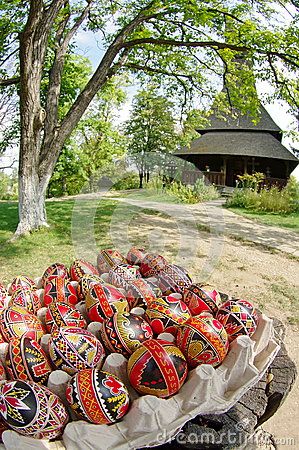 Easter. Hand painted eggs and traditional orthodox wooden church Barsana Monastery - landmark attraction in Maramures, Romania