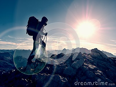 Lens flare defect. Tourist guide on trekking path with poles and backpack. Experienced hiker