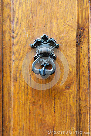 Bronze knocker on old wooden door in Florence
