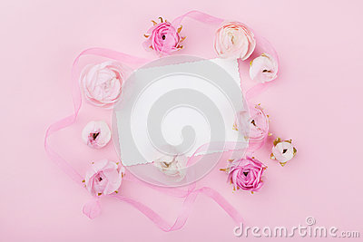 White paper blank and spring flower on pink desk from above for wedding mockup or greeting card on womans day. Floral frame.