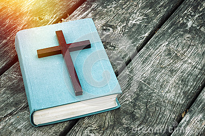 Closeup of wooden Christian cross on bible, burning candle and prayer beads on the old table.