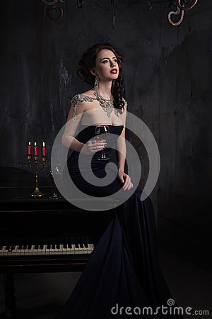 Beautiful young woman in black dress next to a piano with candelabra candles and wine, dark dramatic atmosphere of the castle.