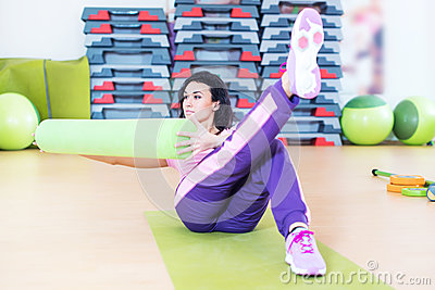 Fit woman doing abs workout exercise russian twists with raised leg