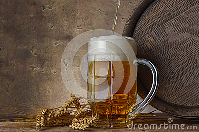 Beer mug with wheat ears and wooden barrel on a dark wall background, pour beer