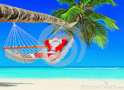 Santa Claus relax in hammock at island palm tropical beach