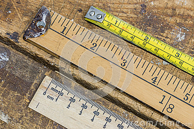 Old yard stick, ruler and tape measure on scratched workshop tab