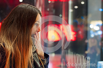 Window shopping, woman looking at the store. Smiling woman pointing at the shop window before entering stor.