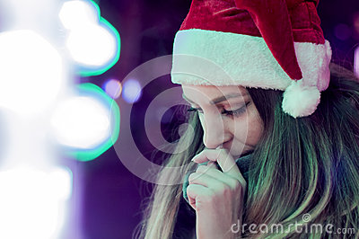 Sad woman by the christmas tree contemplating. Lonely Christmas