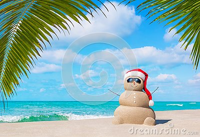 Sandy Snowman in Christmas Santa hat and sunglasses at palm beach
