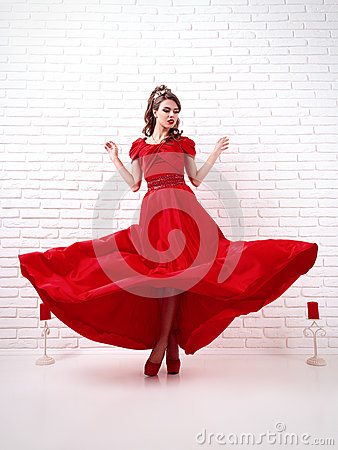 Elegant woman in a long flittering red dress is standing in a wh
