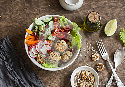 Baked quinoa meatballs and vegetable salad on a wooden table, top view.  Buddha bowl. Healthy, diet, vegetarian food concept.