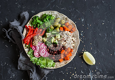 Vegetarian food bowl. Quinoa, beans, sweet potatoes, broccoli, peppers, olives, cucumber, nuts - healthy lunch. On the dark table
