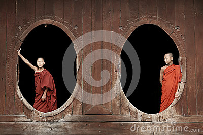 Inle Lake Myanmar, young monks at a Buddhist monastery standing in oval windows