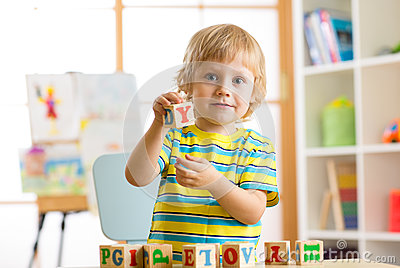 Little preschooler kid boy playing with toy cubes and memorizing letters. Early education and preschool concept