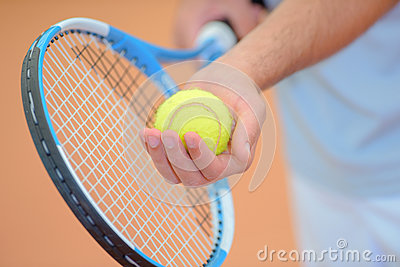 Closeup hands holding tennis racket and ball poised to serve