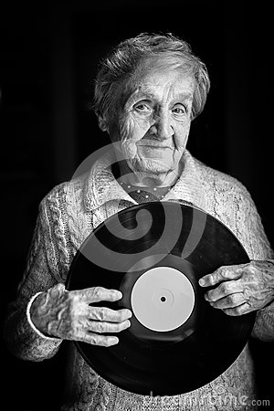 Elderly woman is holding a vinyl record.