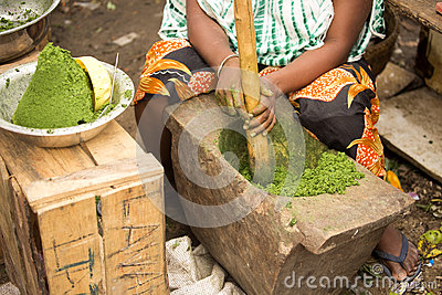 Woman at the market to crush them in the primitive tools of spices, Nosi Be, Madagascar