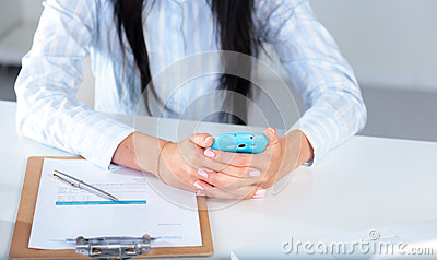 Woman working on celphone, sitting at the desk