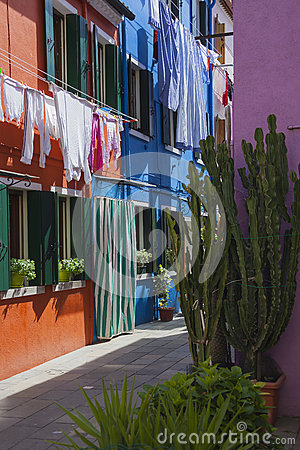 Linen dries above the small street of colorful Burano