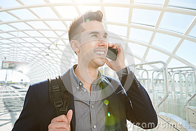 Smiling business man on mobile phone call with bag