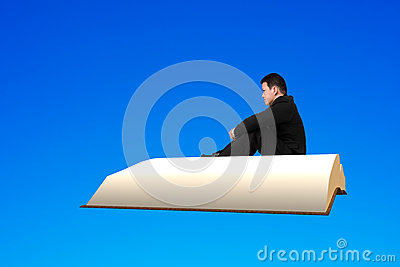 Man sit on book flying in the blue sky