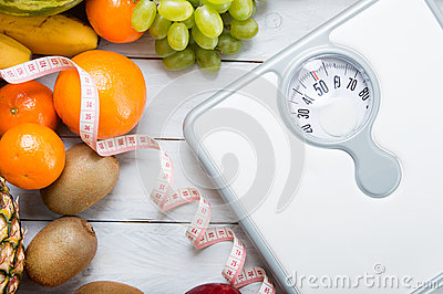 Stack of fruits, white weight scale and tailor meter