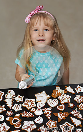 Little child decorating cookies with icing