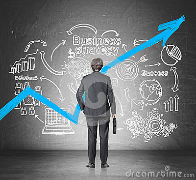 Businessman with a suitcase looking at a growing blue graph and a business strategy sketch.