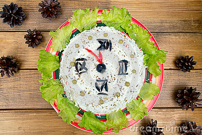 The Christmas salad rice olives greens peas - concept New year clock face, midnight, brown wooden background spruce