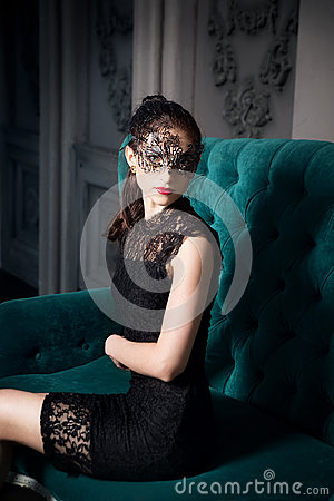 Mysterious woman in venetian carnival mask sitting in sofa in interior