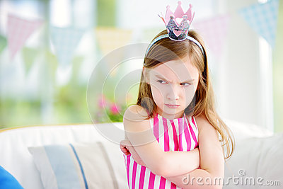 Moody little girl wearing princess tiara feeling angry and unsatisfied