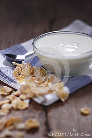 Plain yogurt in small glass bowl with crispy cereal