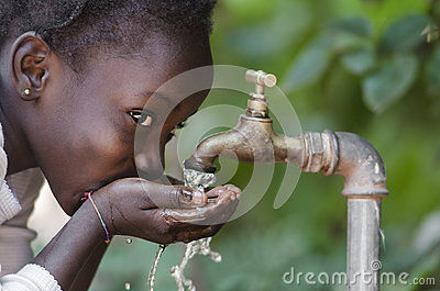 Beautiful African Child Drinking from a Tap Water Scarcity Symbol