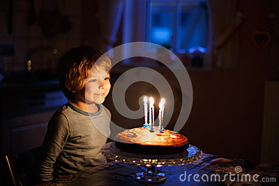 Little kid boy celebrating his birthday and blowing candles on cake
