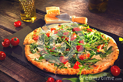 Pizza Caprese with arugula, cheese, yoghurt and cherry tomatoes