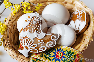 white eggs in wicker nest with decorated gingerbread hen cake with dogwood flower