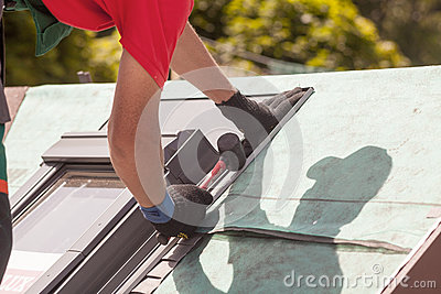 Roofer installs metal profile on a roof window with a rubber mallet.