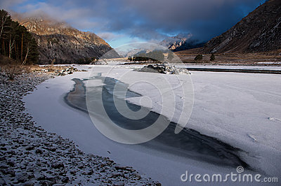 Ice-hole in ice-covered river on the background of a colorful sunrise and high rocks, Altai mountains