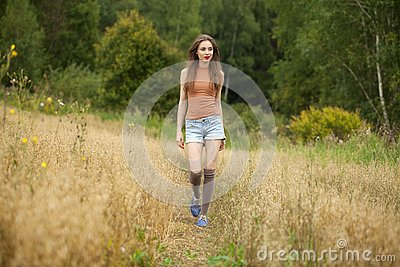 Young beautiful woman walking in a field, summer outdoors