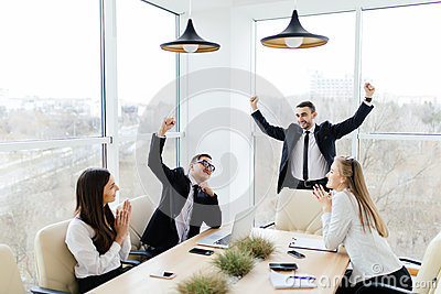 Business people in formalwear celebrate victory  while sitting together at the table