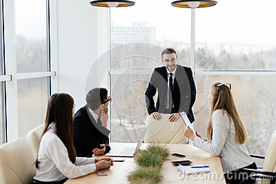 Business people in formalwear discussing with leader something while sitting together at the table