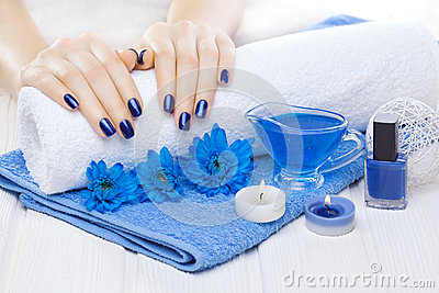 Beautiful blue manicure with chrysanthemum and towel on the white wooden table. spa