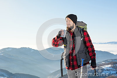 Man drinking from a hip flask on a hiking trip