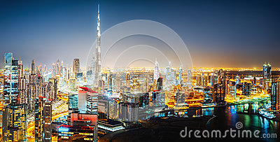 Nightttime skyline of a big futuristic city by night. Business bay, Dubai, United Arab Emirates.