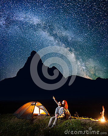 Romantic couple hikers looking at the shines starry sky at night. Happy pair sitting near camp and campfire